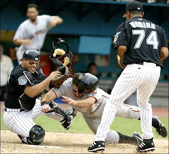 J.T. Snow collides with catcher Ivan Rodriguez during Game 4 of the 2003 NLDS. After tagging Snow, Rodriguez and the Marlins won 7-6 and advanced to the NLCS.
