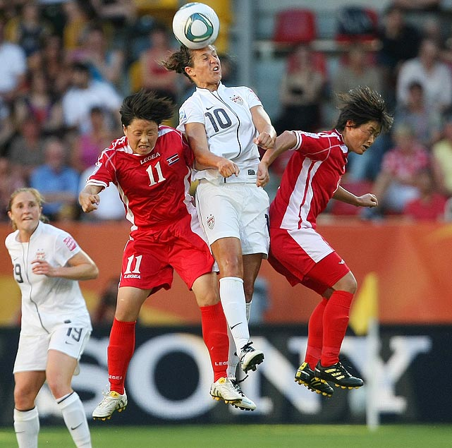 Carli Lloyd goes up for a header against two North Korean players.
