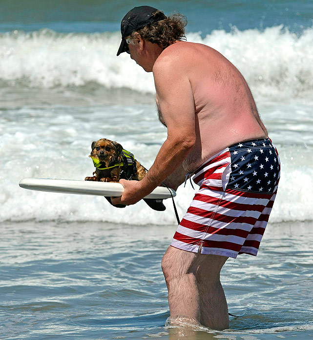 This guy shows off his love for America and his surfing dog, Mr. Tuff, as he waits for a wave during the Loews Surf Dog Competition in Imperial Beach, California.