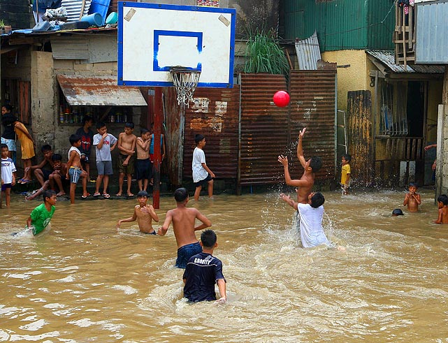 Life goes on after the Philippines were hit by back-to-back storms that caused heavy rains and flooding; the waist-deep water does not stop these ballers from balling.