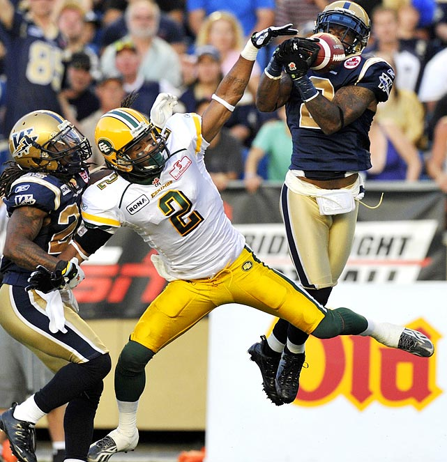 Winnipeg Blue Bombers' Jovon Johnson snags the ball from intended receiver Fred Stamps of Edmonton during their CFL game.