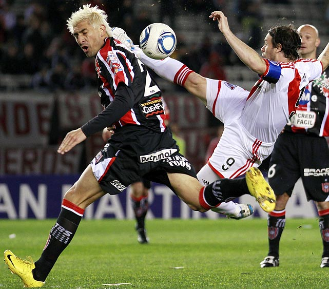 River Plate's Fernando Cavenaghi leaps for the ball as Chacarita Juniors' Javier Paez reacts to Cavenaghi's move during their Argentine National B second division soccer match in Buenos Aires.