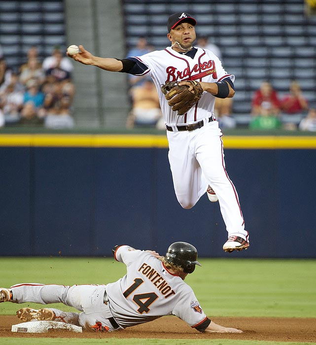 Atlanta Braves shortstop Alex Gonzalez turns a double play while leaping over San Francisco Giants shortstop Mike Fontenot at Turner Field.