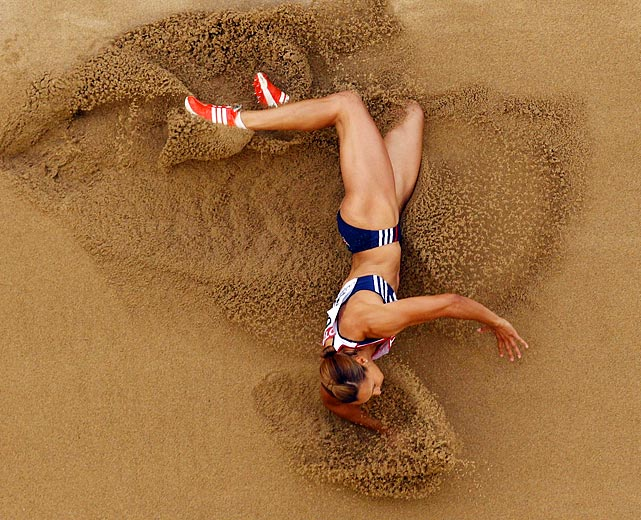 Britain's Jessica Ennis, favored in the heptathlon, falls in the sand after a long jump attempt. Ennis, who held the lead at one point during the event, took the silver medal.
