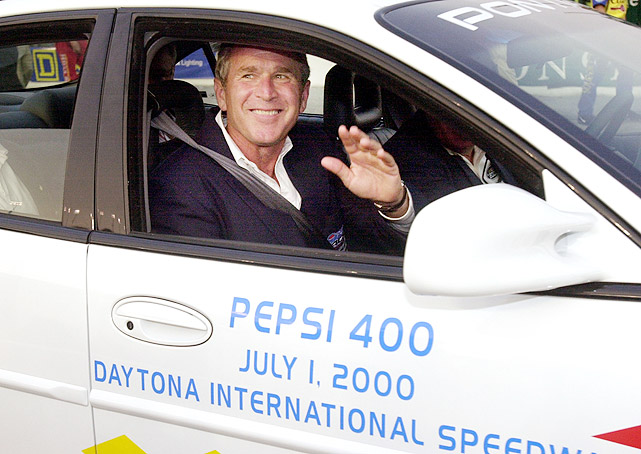 Then-Republican presidential candidate George W. Bush waves as he rides around in the pace car during the Pepsi 400 at Daytona on July 1, 2000. Bush served as the grand marshal of the event.