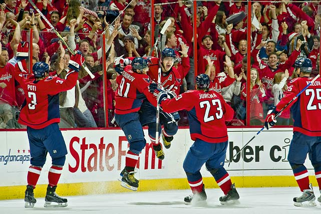 "Capitals forward Alex Ovechkin celebrates his hat trick goal with teammates during Game 2 of their Eastern Conference Semifinals against the Penguins.   Quote from Capozzola: ""If you asked me to describe Alex Ovechkin's style of play in three words or less they would be: dynamic, explosive and enthusiastic. Add the intensity of a playoff game and a hat trick to boot, those ingredients combine to make an image reflective of his passion for the game. He's fun to watch, a joy and a challenge to photograph, and he brings smiles to a lot of faces."""