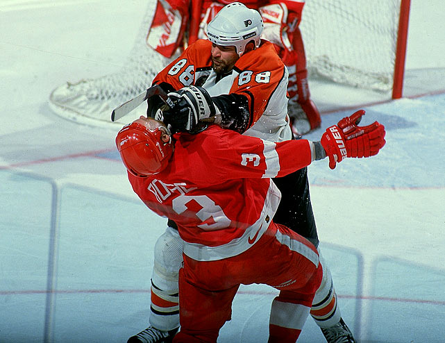 Flyers center Eric Lindros checks Red Wings defenseman Bob Rouse during the third period of Game 2 of the 1997 Stanley Cup Finals.