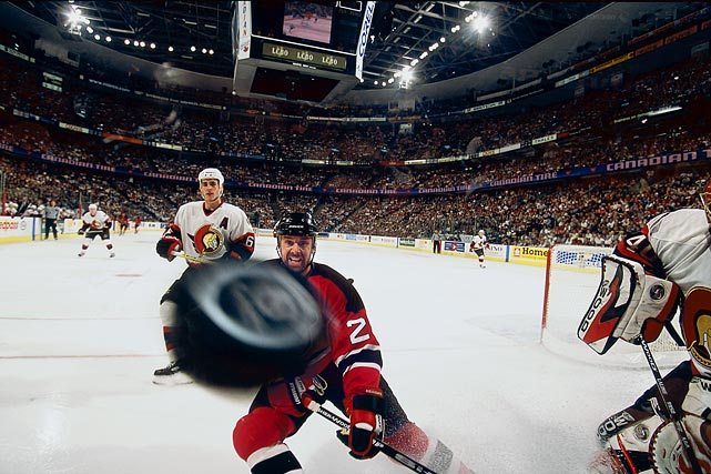 Devils center Joe Nieuwendyk and Senators defenseman Wade Redden watch the puck go around the corner glass after being moved by Sens goalie Patrick Lalime during the first period of Game 1 of the Eastern Confernce Finals.