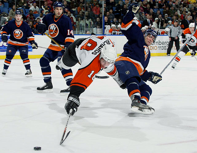 Flyers center Mike Richards reaches for the puck as he is upended by Islanders defenseman Sean Hill.