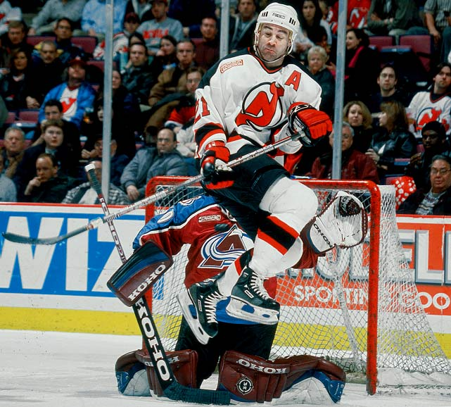 Devils right wing Randy McKay jumps to avoid being hit by a teammate's shot while playing at the top of Avalanche goalie Marc Denis' crease during the second period.