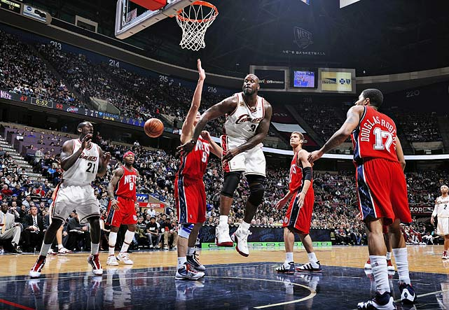 Cavaliers center Shaquille O'Neal makes a no look pass to teammate J.J. Hickson around Nets forward Yi Jianlian.