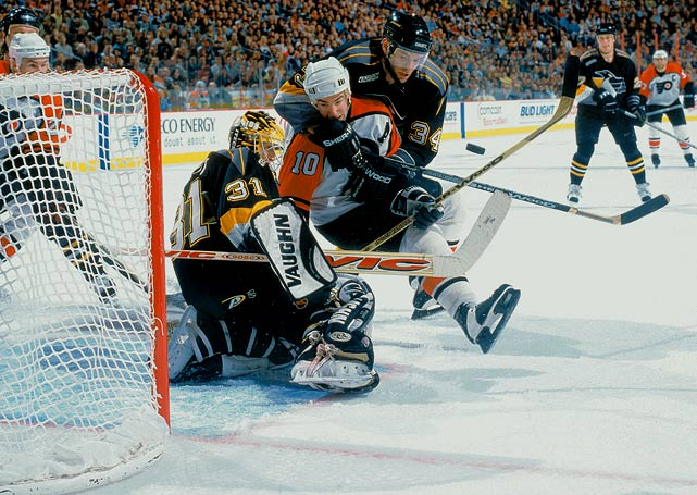 Flyers left wing John LeClair is brought down in front of the net by Penguins defenseman Peter Popovic as Pens goalie Ron Tugnutt makes a save during the second period of Game 1 of their Eastern Conference Semifinals.