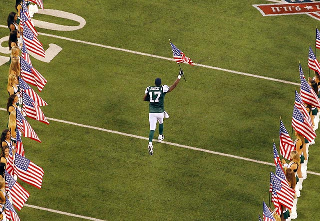 Plaxico Burress runs onto the field carrying a U.S. flag during pregame ceremonies to mark the 10-year anniversary of the 9/11 attacks.