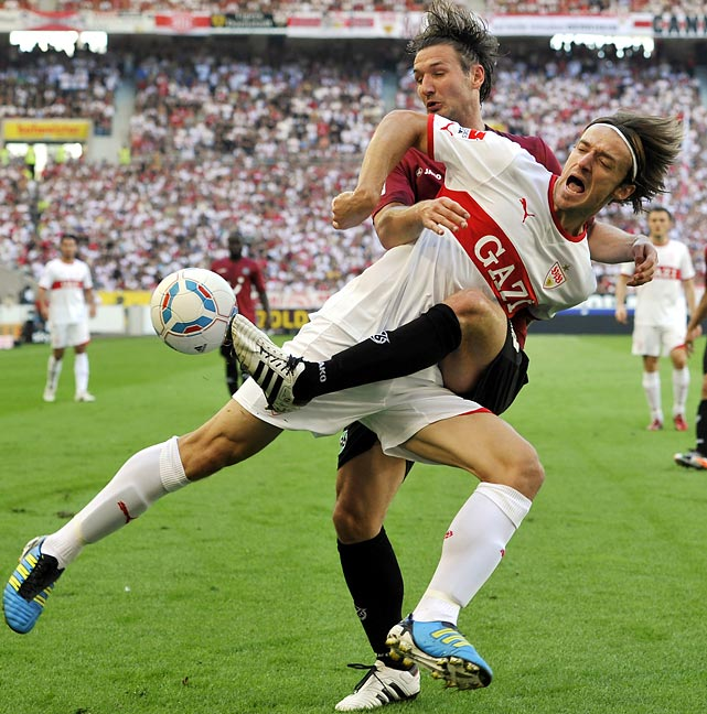 As Stuttgart's Christian Gentner (front) attempts to escape the ball, Hanover's Christian Schulz reaches around, appearing to hug Gentner, but really sneaking a toe on the ball.