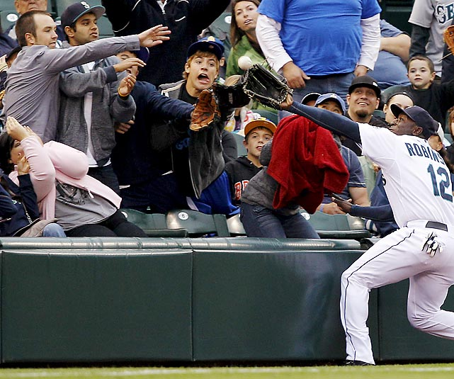 Seattle left fielder Trayvon Robinson makes a daring catch on a foul ball hit by Texas Rangers' outfielder David Murphy. The Mariners would lose the Sept. 17 game 7-6.