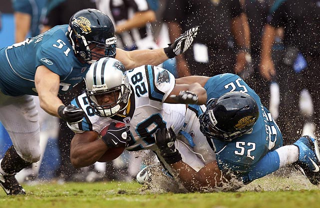 Jacksonville Jaguars' linebackers Daryl Smith (52) and Paul Posluszny team up to bring Panthers' running back Jonathan Stewart down on the soaked Bank of America Stadium grass.