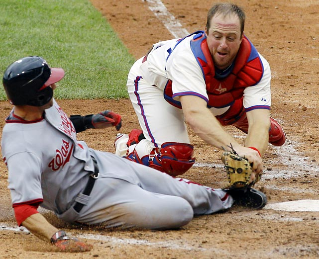 Phillies catcher Erik Kratz makes a lunging tag before Stephen Lombardozzi of the Washington Nationals can reach home plate.