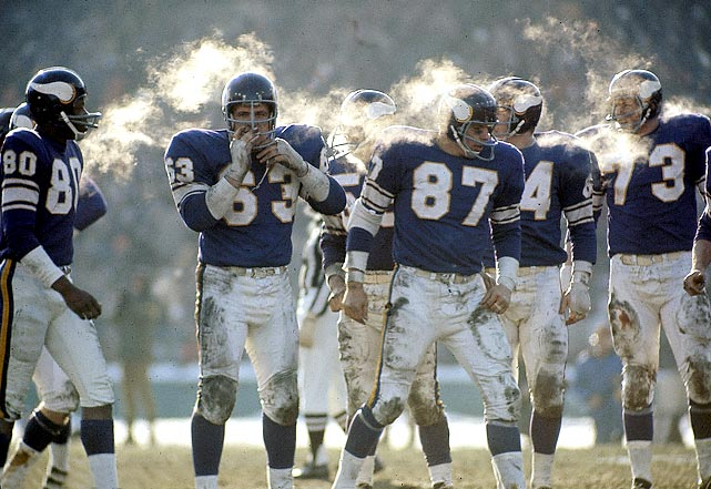 There is no comfort in midwinter in Minnesota, as these Vikings know all too well. Guard Jim Vellone (#63) tries blowing on his hands to warm them up, while his teammates gather to brace themselves for the next bruising play.