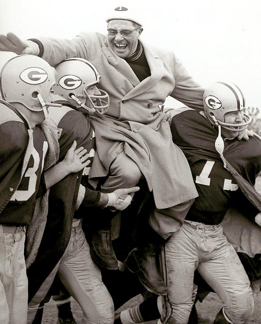 After winning his first NFL title, an overjoyed Vince Lombardi is carried off the field by three of his players: (left-right) Jim Taylor, Paul Hornung and Forrest Gregg.