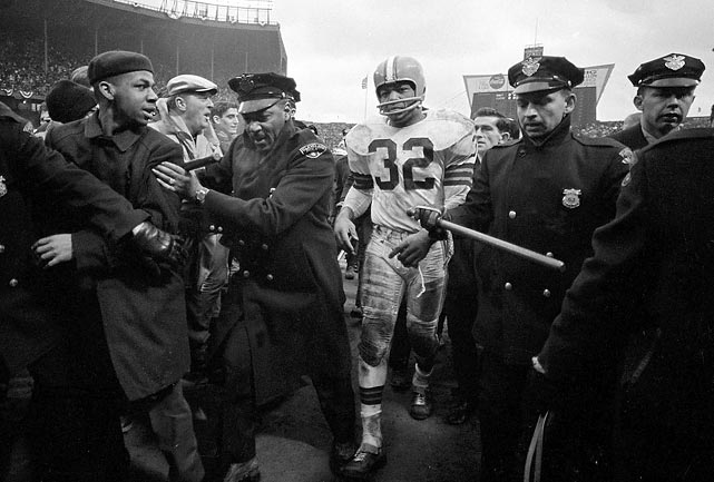 After spending the afternoon powering his way through the Baltimore defense, Jim Brown has a clear path through the awed crowd, thanks to a police escort, and his trademark glare.