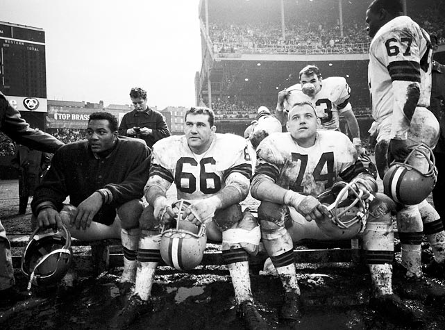 With the game well in hand, Jim Brown (left) relaxes on the bench next to two other big contributors to the Browns' championship season - guard Gene Hickerson (#66) and defensive tackle Dick Modzelewski (#74).