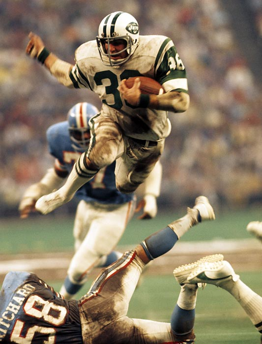 Jets running back John Riggins (#36) hurdles fallen Oilers linebacker Ron Pritchard. After five years with the Jets, the versatile runner and receiver joined the Redskins, becoming one of the NFL's top stars, scoring 24 touchdowns in 1983.