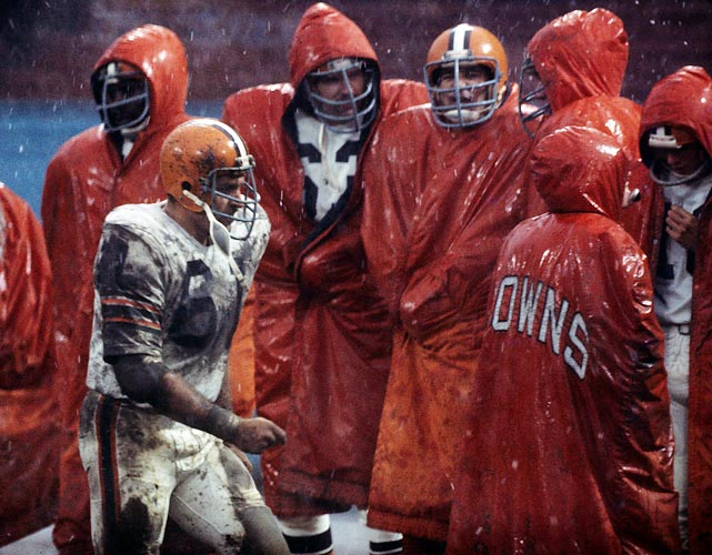 The Browns shiver on the sidelines while guard Bob DeMarco (#61) looks for his parka so he can join them.