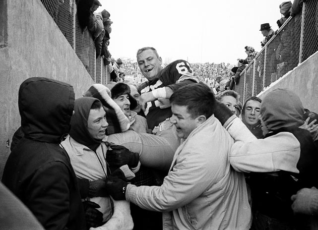 Packers linebacker Tom Bettis, sporting the scars of a gridiron gladiator, gets a hero's escort off the field from fans overjoyed at the 37-0 triumph.