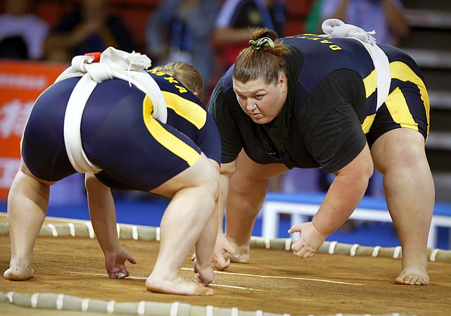 Open weight sumo wrestler Olga Davydko glares at her opponent before the start of their match, hoping to up the intimidation factor. Unlike Greco Roman wrestling, which is contested at the Olympics and scored based on performance, sumo wrestlers try to force their opponents to touch the ground with any body part other than the soles of their feet, or push them out of the wrestling ring. Most matches only last a few seconds, but some can last several minutes.