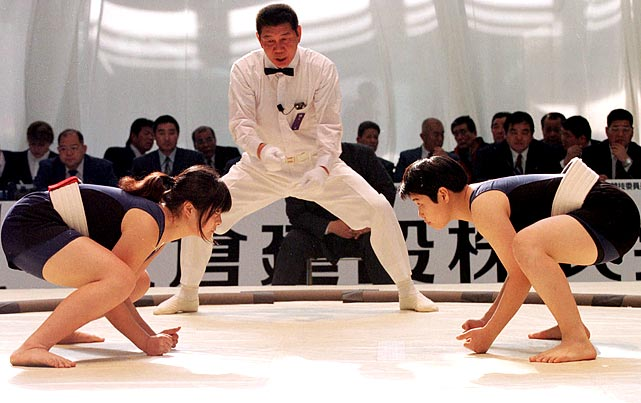 As the referee calls a start, Azumi Okada (right) and Eriko Kawai gaze at each other on the sumo mound.