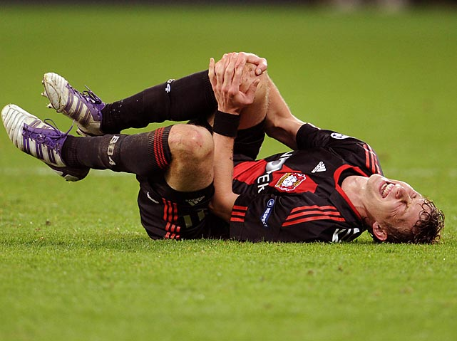 Stefan Kießling of Bayer Leverkusen grasps his knee in what may or may not be an actual injury.