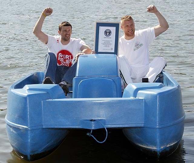 "Former England cricketer Andrew ""Freddie"" Flintoff (right) and friend Steve Harmison celebrate with their official certificate after a successful attempt to break the fastest 100m in a pedalo world record on Hyde Park boating lake in London."