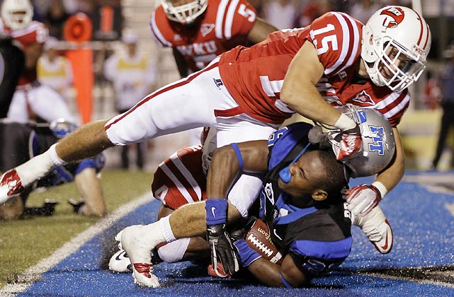Western Kentucky defensive back Bryan Beard (15) scores a safety for his team and separates Middle Tennessee running back William Practcher from his helmet. Beard's team won 36-33.