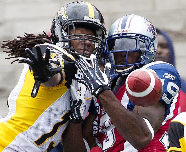 Cornerback Woodny Turenne (left) of the Hamilton Tiger-Cats defends Montrel Alouettes receiver S.J. Green during a CFL game.