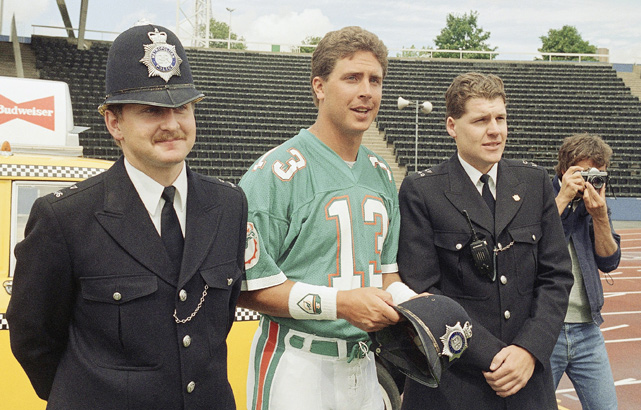 Former Miami quarterback Dan Marino is escorted off of the Wembley Stadium field for attempting to play football on it.