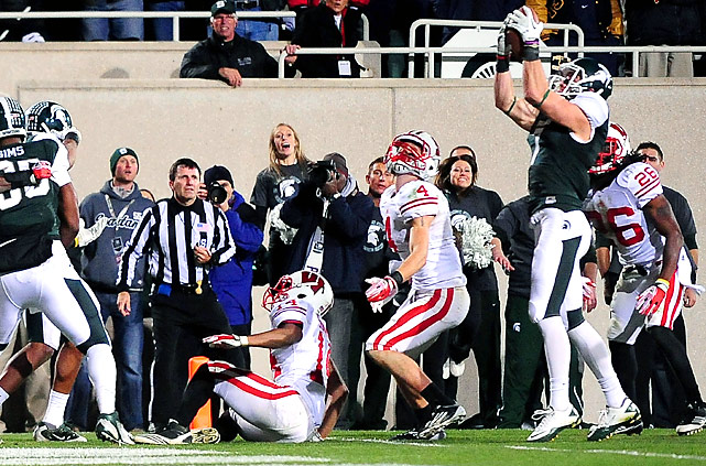 Michigan State's Keith Nichol (right) caught a 44-yard desperation heave from Kirk Cousins on the game's final play for a tiebreaking touchdown, stunning Wisconsin.  With four seconds left, Cousins rolled out to his right and threw it about as far as he could. The ball went into the end zone but caromed off Michigan State receiver B.J. Cunningham's facemask back to Nichol, who caught it just outside the end zone and struggled for the goal line, fighting two Wisconsin defenders and just barely breaking the plane.