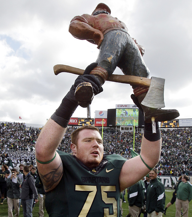 Offensive tackle Jared McGaha hoists the Paul Bunyan Trophy, which now belongs to Michigan State for the fourth straight year after the Spartans defense held the Wolverines to 223 yards below their season average.