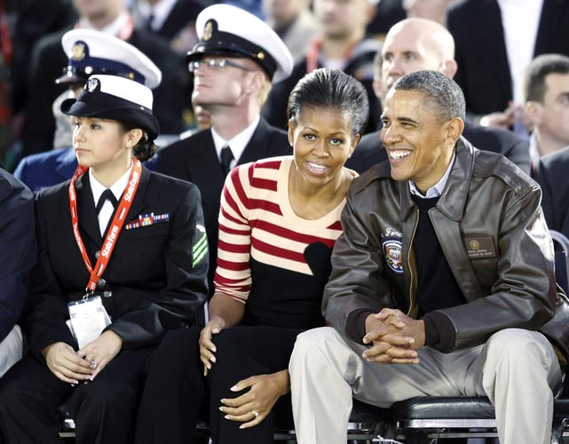 President Barack Obama and First Lady Michelle Obama sit courtside during the Carrier Classic.
