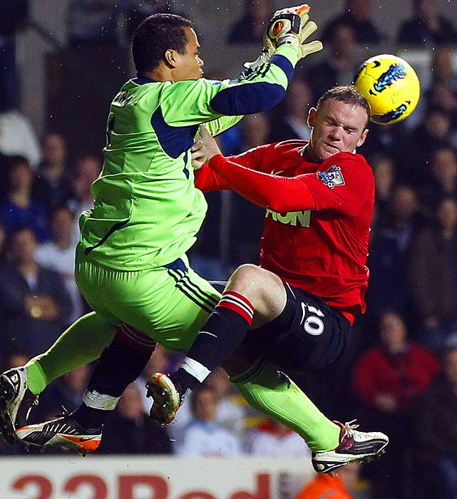 Swansea City goalkeeper Michel Vorm knocks a ball away from Manchester United striker Wayne Rooney during an English Premier League soccer match. Rooney's club won 1-0.