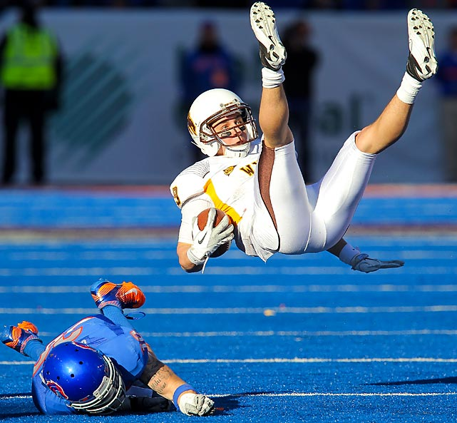 Boise State safety Travis Stanaway (bottom) upends Wyoming receiver Sam Stratton on the blue turf of Bronco Stadium during Boise State's 36-14 victory over the Cowboys.