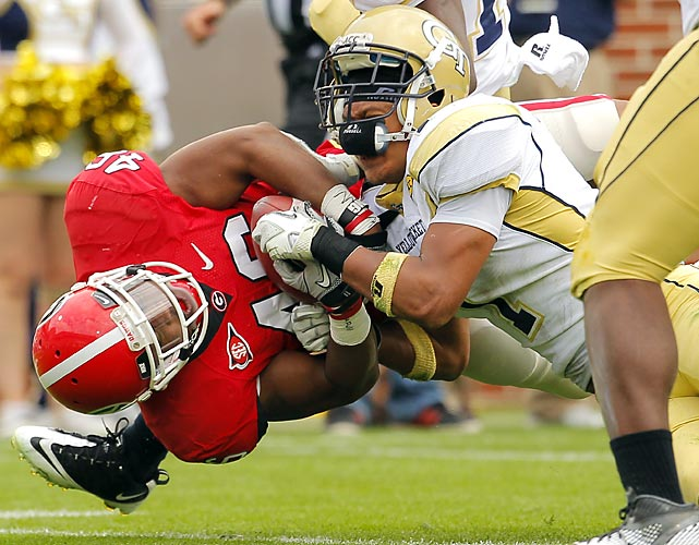Georgia fullback Alexander Ogletree (left) holds onto the ball as Georgia Tech safety Isaiah Johnson wrestles him to the ground. The Bulldogs beat the Yellow Jackets 31-17.