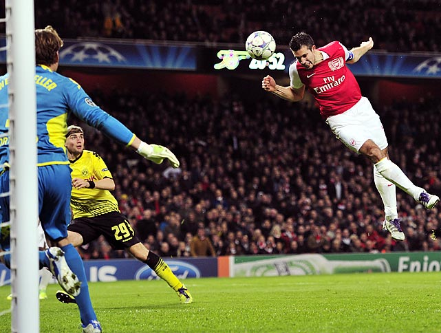 Arsenal striker Robin Van Persie heads in a goal during a UEFA Champions League match against Borussia Dortmund. Arsenal won 2-1.