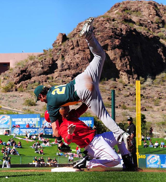 The Angels' Jean Segura practically tackles the A's Andy LaRoche at third base during a spring training game.