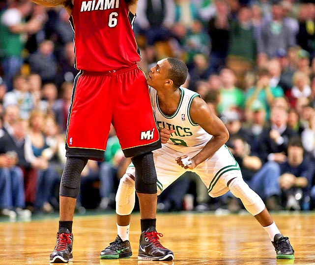 Celtics' Rajon Rondo peers up at the Heat's LeBron James while defending down below.