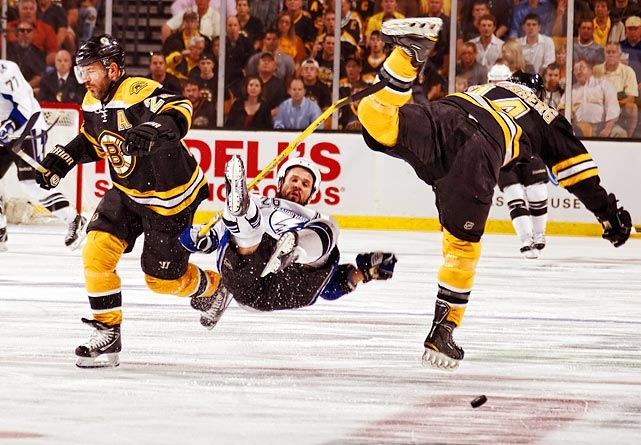Boston Bruins Mark Recchi (left) and Dennis Seidenberg (right) check Martin St. Louis of the Tampa Bay Lightning.