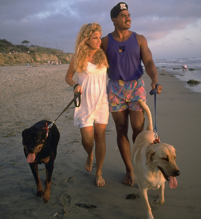 Chargers linebacker Junior Seau and his wife walk their dogs on the beach in 1993. Seau married Gina Deboer in 1991; they divorced in 2002.