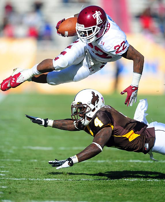 Temple running back Matt Brown tries to jump over Wyoming safety Tashaun Gipson during the New Mexico Bowl. The Owls won 37-15.