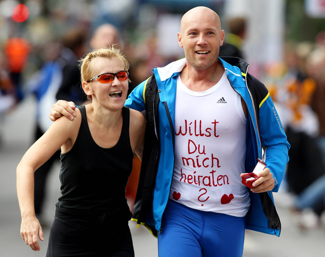 Mark Auer runs alongside marathon runner Eva Mary Kubin with a shirt that contains a marriage proposal written in German.