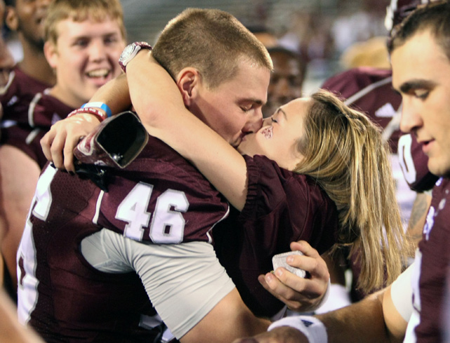Mississippi State long snapper Aaron Feld kisses his fiance Blakely Bailey. She accepted his marriage proposal after a game against UAB.