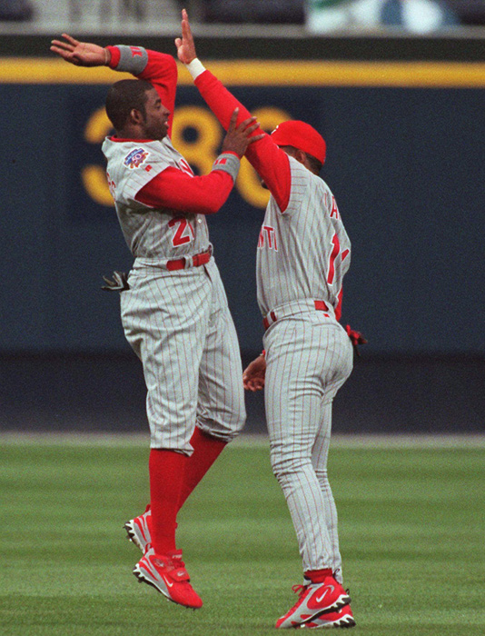 Larkin (right) shares a lighter moment with Reds teammate Deion Sanders before playing the Braves in April 1997.